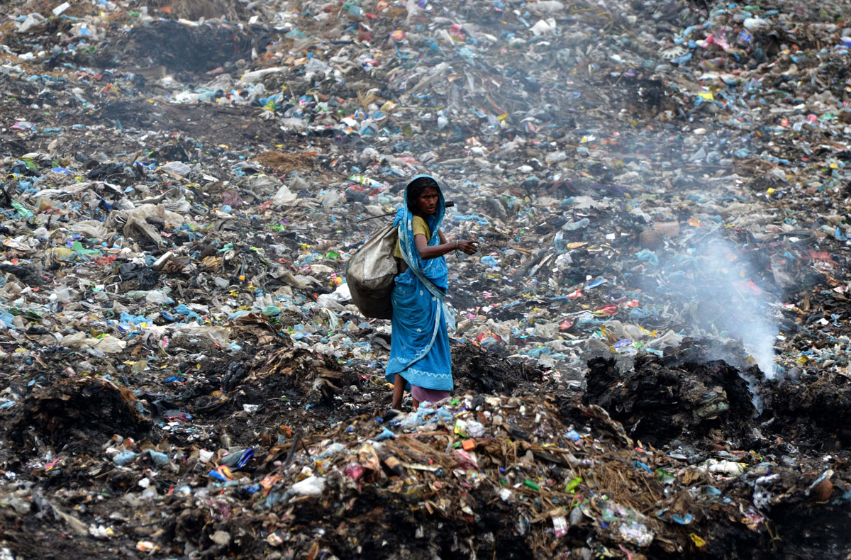 An Indian ragpicker walks among heaps of rubbish at a municipal waste dump in Dimapur on April 22, 2013, on World Earth Day. Earth Day is observed each April 22, during which events are held worldwide to demonstrate support for environmental protection. AFP PHOTO/STRSTRDEL/AFP/Getty Images ORG XMIT: